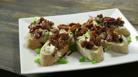 antipasti : Italian food. Bruschetta with dried tomatoes, mozzarella cheese, balsamico sauce, green onion. 4K