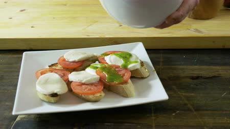 white onion : Chef cooking italian food. Bruschetta with tomatoes, mozzarella cheese, pesto sauce, green onion. 4K