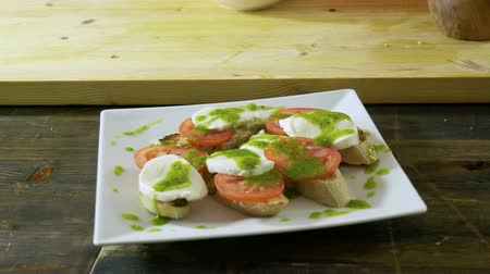 стартер : Chef cooking italian food. Bruschetta with tomatoes, mozzarella cheese, pesto sauce, green onion. 4K