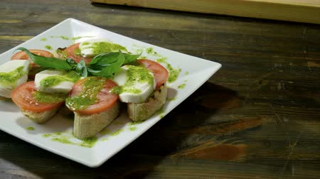 cebolinha : Italian food. Bruschetta with tomatoes, mozzarella cheese, pesto sauce, green onion, fresh basil. 4K Vídeos
