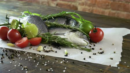 lezzet : Ingredients for cooking fish. Fresh sea bass, green onions, lime, garlic cloves, rosemary, seasoning. 4K Stok Video