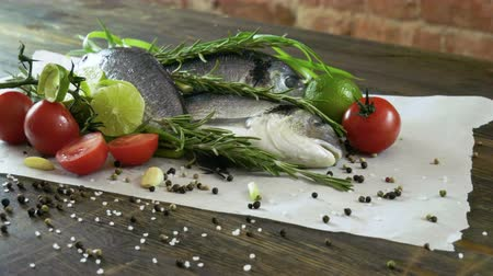 lyme : Ingredients for cooking fish. Fresh sea bass, green onions, lime, garlic cloves, rosemary, seasoning. 4K Stock Footage