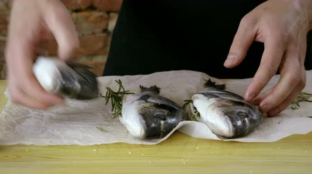 baking dishes : Cooking of three sea bass. Close-up shot of cook preparing fresh fish for baking. 4K