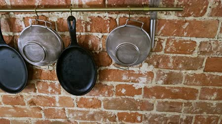 panelas : Kitchen interior. Panorama of cast iron frying pans, sieves, whisk, wooden cutting boards on brick wall background. 4K