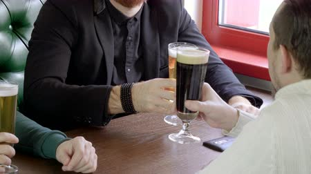 cheers : Three good old friends drinking beer in a pub. 4K Stock Footage