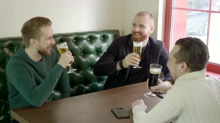 quartilho : The young smiling men clinking glasses of beer in a pub. 4K Stock Footage