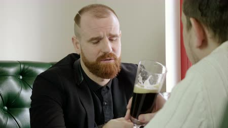 cidra : Portrait of redhead man with a beard drinking beer with friends in a pub. 4K