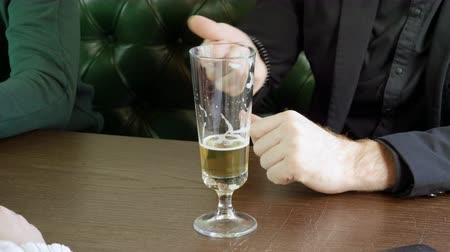 alkoholos : Close-up shot of one glass of light beer is being hold in mens hands. 4K Stock mozgókép