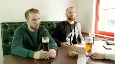 pistache : Meeting of friends. A company of handsome men are talking and drinking beer in a restaurant. 4K