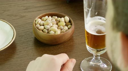 cidra : Close-up shot of male hands with glass of beer and bowl with pistachios in the pub. 4K