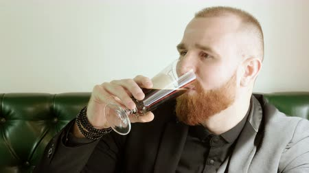 cidra : Close-up shot of redhead man with a beard drinking beer and talking with friends in a pub. 4K