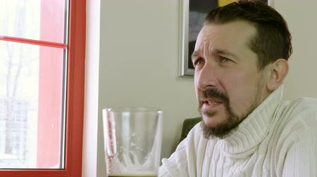 pult : Close-up shot of dark man with a beard drinking beer and talking with friends in a pub. 4K