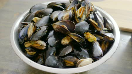 małże : Fresh shellfish seafood. Close-up of bowl with raw mussels in opened shells. 4K