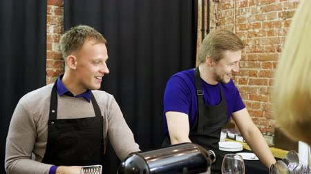 körítés : Two young men and two women talking, cooking a meal at cooking master class. 4K