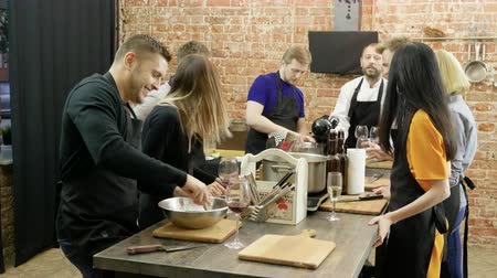 master class : A group of people talking, laughing, preparing a food at cooking master class. 4K