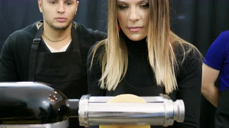 massa : Blonde pretty woman rolling out dough for macaroni using the pasta machine. 4K Vídeos