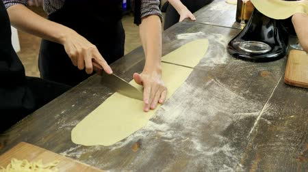 kasza manna : Close-up shot of female hands cutting the rolled dough on parts for pasta. 4K