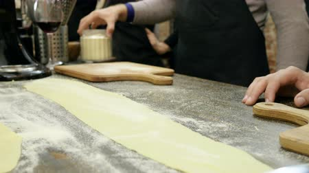 búzadara : Close-up shot of male hands cutting the rolled dough on parts for the pasta. 4K