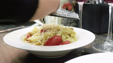 grated : Womens hands grating parmesan cheese on a ready pasta with tomatoes, almonds and pesto sauce on a white plate. 4K Stock Footage