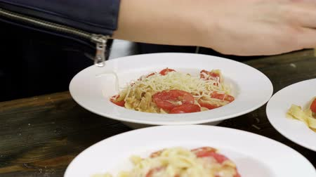 panelas : Womens hands rubbing parmesan cheese on a cooked pasta with tomatoes, almonds and pesto sauce on a white plate. 4K Stock Footage
