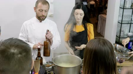 kuchenka : A group of people putting a spaghetti in a steel pot with boiling water at cooking master class. 4K Wideo