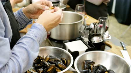 bivalve : A group of people preparing mussels with cream at the cooking master class. 4K