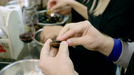 shellfish recipe : A group of people preparing mussels with cream at the cooking master class. 4K