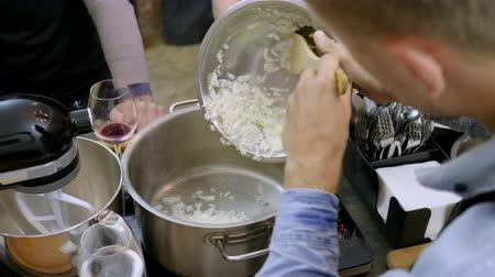 питательный : The man stewing in the pan chopped onion at cooking master class. 4K