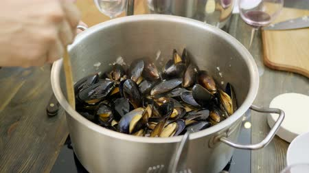 midye : Close-up shot of mussels are being stewed in a saucepan on an electric stove. 4K