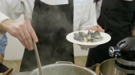eaten : Chef putting cooked mussels in a white plate using a ladle at cooking master class. 4K