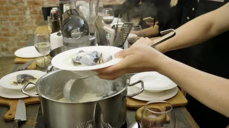 midye : Man putting cooked mussels in a white plate using a ladle at cooking master class. 4K