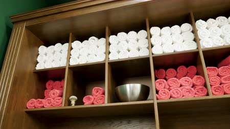 terry : Terry towels lying on wooden shelves in the closet at the barbers. 4K Stock Footage
