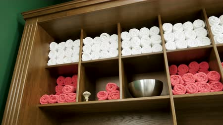 šatník : Terry towels lying on wooden shelves in the wardrobe in the barbershop. 4K