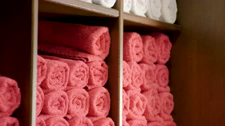terry : Terry towels lying on wooden shelves in the wardrobe in the barbershop. 4K