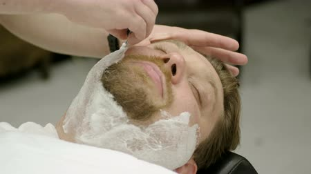 shaver : Shaving of beard. Barber cutting mens face hair with straight razor at barbershop. 4K