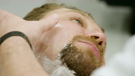 shaving foam : Shaving of beard. Barber cutting mens face hair with straight razor at barbershop. 4K