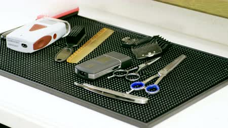 бритье : Shaving accessories. Close-up shot of barbers tools. Scissors, combs, razor, electric shaver in barbershop. 4K