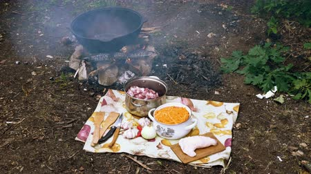 kocioł : Cooking of pilaf in a large cast-iron cauldron on the fire. Ingredients for pilau. 4K