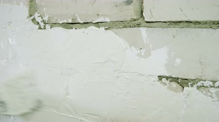 миномет : House renovation. Close-up shot of womens hand applying putty on the brick wall. 4K