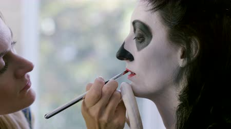 catrina : Halloween party. Make-up artist is making woman up as skeleton for celebration of the Mexican Day of the Dead. 4K