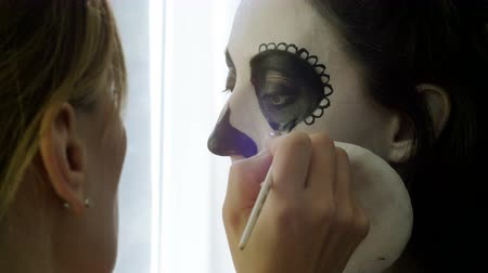 duch : Halloween party. Make-up artist is making woman up as skeleton for celebration of the Mexican Day of the Dead. 4K