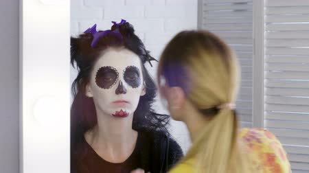 deceased : Halloween face art. Make-up artist is making woman up as skeleton for celebration of the Mexican Day of the Dead. 4K