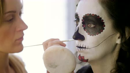 catrina : Halloween face art. Make-up artist is making woman up as skeleton for celebration of the Mexican Day of the Dead. 4K