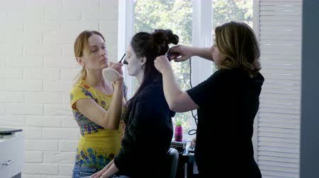 tongs : Make-up artist and hairstylist making makeup and curly hair to young brunette woman for halloween. 4K