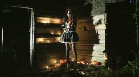 косплей : The Mexican Day of the Dead. The young woman with scary skeleton halloween make-up holding a lighted candle. HD