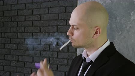 zapalovač : Portrait of handsome man wearing in a black suit, lighting and smoking a cigarette. 4K