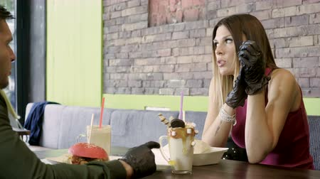 date dating : Young beautiful woman and man smiling, talking, eating two hamburgers and drinking two soft drinks in cafe. 4K Stock Footage