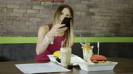 delici : Young blonde beautiful woman taking photo of her dinner: two burgers and two soft drinks in cafe. 4K Stok Video