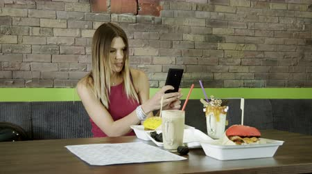 pronikavý : Pretty woman taking photo of her fast food: two hamburgers and two milk shakes in restaurant. 4K