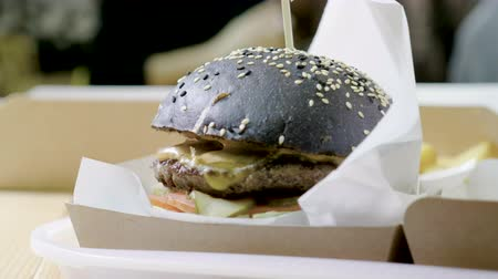 dana eti : Burger. Close-up shot of black hamburger with beef cutlet and french fries. 4K